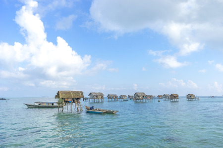 lived here: SABAH, MALAYSIA - AUGUST 15, 2016 : Poor floating house at Bodgaya Island, Sabah, Malaysia. They lived in a house built on stilts in the middle of sea, boat is the main transportation here.