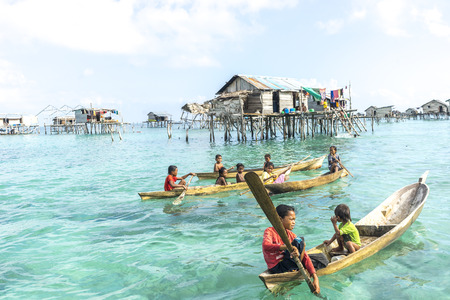 lived here: SABAH, MALAYSIA - AUGUST 17, 2016 : Unidentified Bajau Laut kids on a boat in Bodgaya Island, Sabah, Malaysia. They lived in a house built on stilts in the middle of sea, boat is the main transportation here.
