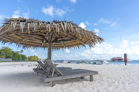 loungers: Dreamy beach with sun loungers under a beach umbrella at Mabul, Semporna Sabah Stock Photo
