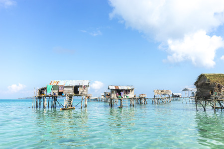 lived here: SABAH, MALAYSIA - AUGUST 17, 2015 : Bajau Laut house in Bodgaya Island, Sabah, Malaysia. They lived in a house built on stilts in the middle of sea, boat is the main transportation here