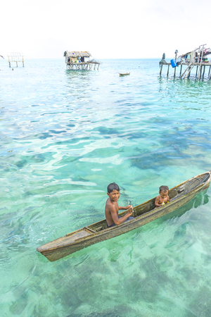 stilt: SABAH, MALAYSIA - AUGUST 15, 2015 : Unidentified Bajau Laut kids on a boat in Bodgaya Island, Sabah, Malaysia. They lived in a house built on stilts in the middle of sea, boat is the main transportation here. Editorial