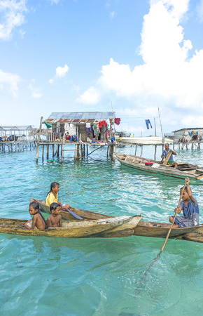 lived here: SABAH, MALAYSIA - AUGUST 15, 2016 : Unidentified Bajau Laut kids on a boat in Bodgaya Island, Sabah, Malaysia. They lived in a house built on stilts in the middle of sea, boat is the main transportation here.