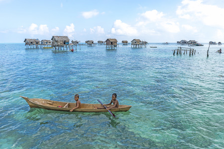 lived here: SABAH, MALAYSIA - AUGUST 15, 2015 : Unidentified Bajau Laut kids on a boat in Bodgaya Island, Sabah, Malaysia. They lived in a house built on stilts in the middle of sea, boat is the main transportation here. Editorial
