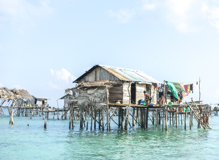 lived here: SABAH, MALAYSIA - AUGUST 17, 2016 : Bajau Laut house in Bodgaya Island, Sabah, Malaysia. They lived in a house built on stilts in the middle of sea, boat is the main transportation here.