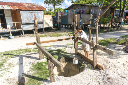 mabul: MABUL ISLAND, MALAYSIA - AUGUST 16, 2016 : View of poor wooden house and villagers at Mabul Island, Malaysia. The young boy take the water from well. Editorial