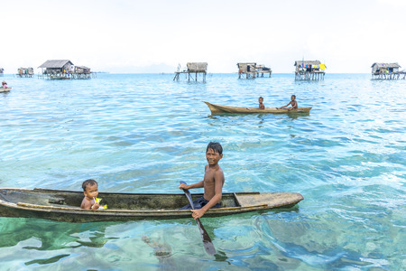lived here: SABAH, MALAYSIA - AUGUST 15, 2015: Unidentified Bajau Laut kids on a boat in Bodgaya Island, Sabah, Malaysia. They lived in a house built on stilts in the middle of sea, boat is the main transportation here