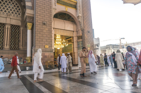 ksa: MEDINA, KINGDOM OF SAUDI ARABIA (KSA) - MAR 9 : Moslems walk in to babussalam door (main entrance door) at Nabawi Mosque on March 09, 2015 in Medina, KSA. Nabawi Mosque is the second holiest mosque in Islam.