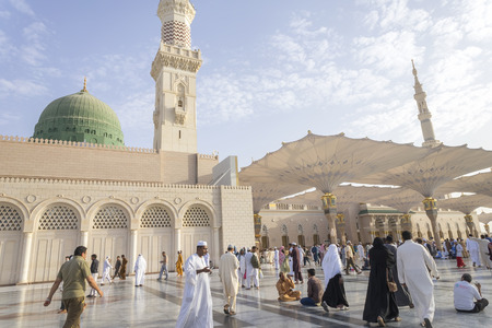 MEDINA, KINGDOM OF SAUDI ARABIA (KSA) - MAR 06: Muslims marching in front of the mosque of the Prophet Muhammad on March 06, 2015 in Medina, KSA. Prophet's tomb is under the green dome.