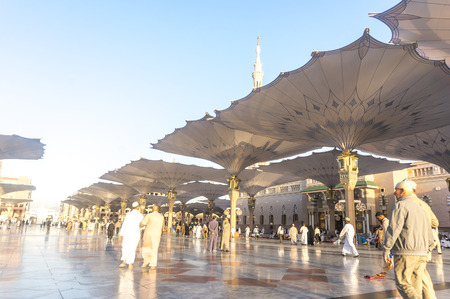 ksa: MEDINA, KINGDOM OF SAUDI ARABIA (KSA) - MAR 9 : Moslems walk outside Nabawi Mosque after dusk prayer March 09, 2015 in Medina, KSA. Nabawi Mosque is the second holiest mosque in Islam.