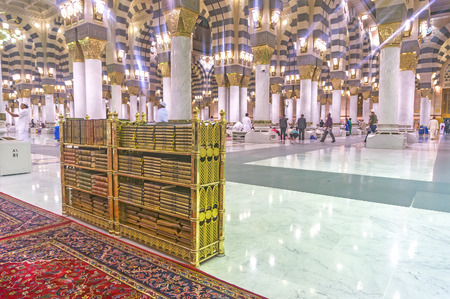 holiest: MEDINA-MAC 9 : Muslims read Quran and pray inside of Masjid Nabawi March 9, 2015 in Medina, Saudi Arabia. Nabawi Mosque is the second holiest mosque in Islam and here is Prophet Muhammad is laid to rest Editorial