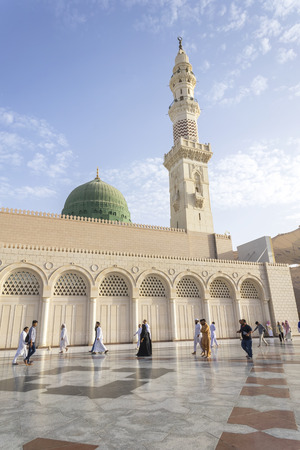 MEDINA, KINGDOM OF SAUDI ARABIA (KSA) - MAR 06: Muslims marching in front of the mosque of the Prophet Muhammad on March 06, 2015 in Medina, KSA. Prophets tomb is under the green dome.