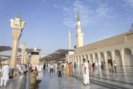 ksa: MEDINA, KINGDOM OF SAUDI ARABIA (KSA) - MAR 06: Muslims marching in front of the mosque of the Prophet Muhammad on March 06, 2015 in Medina, KSA. Prophets tomb is under the green dome.