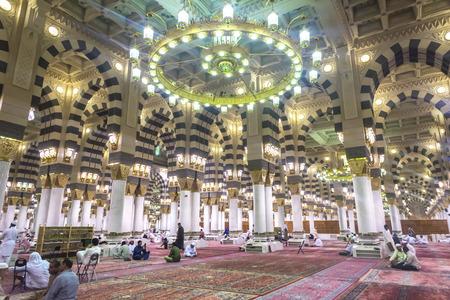 AL MADINAH, KINGDOM OF SAUDI ARABIA - MAR 07: Muslim pray and read Quran inside Masjid (mosque) Nabawi on March 07, 2015 in Al Madinah, S. Arabia. Nabawi mosque is the 2nd holiest mosque in Islam. Editorial