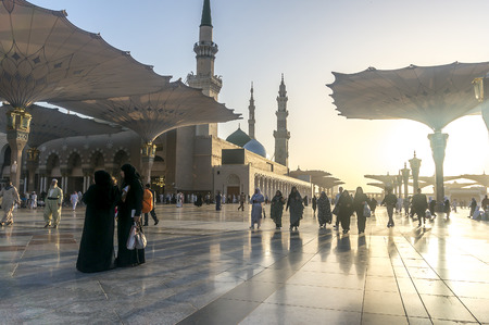 ksa: MEDINA, KINGDOM OF SAUDI ARABIA (KSA) - MAR 9 : Moslems walk outside Nabawi Mosque after fajr prayer March 9, 2015 in Medina, KSA. Nabawi Mosque is the second holiest mosque in Islam. Editorial