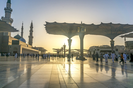 ksa: MEDINA, KINGDOM OF SAUDI ARABIA (KSA) - MAR 9 : Moslems walk outside Nabawi Mosque after fajr prayer March 9, 2015 in Medina, KSA. Nabawi Mosque is the second holiest mosque in Islam. Editorial
