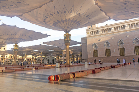 holiest: MEDINA - MARCH 06 : Pilgrims walk underneath giant umbrellas at Nabawi Mosque compound on March 06, 2015 in Medina, Kingdom of Saudi Arabia. Nabawi mosque is the second holiest mosque in Islam. Editorial