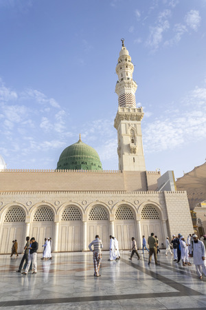 worshiped: MEDINA, KINGDOM OF SAUDI ARABIA (KSA) - MAR 06: Muslims marching in front of the mosque of the Prophet Muhammad on March 06, 2015 in Medina, KSA. Prophets tomb is under the green dome.
