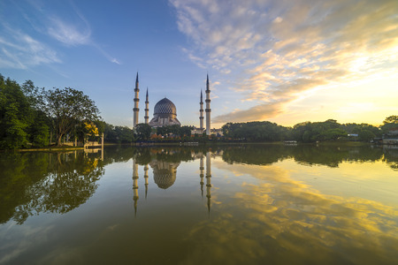 alam: SELANGOR, MALAYSIA - JANUARY 30, 2016: The Beautiful Sultan Salahuddin Abdul Aziz Shah Mosque (also known as the Blue Mosque) with nature sunrise lighting and reflection.