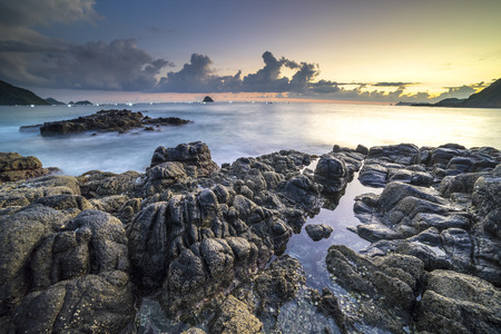 batu: Natural rock with strong water wave and sunrise background at Belanak Beach, Lombok, Indonesia