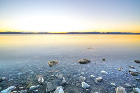 Stone lake with sunrise background.