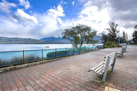 paso de peatones: Una fila de brench de madera delante de Te Anau lago, Nueva Zelanda