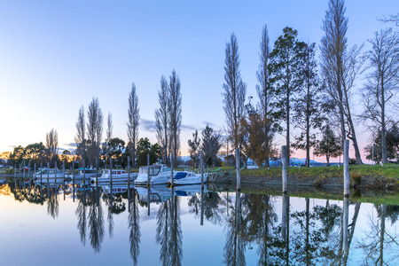 A row of boats with reflection during sunrise moment