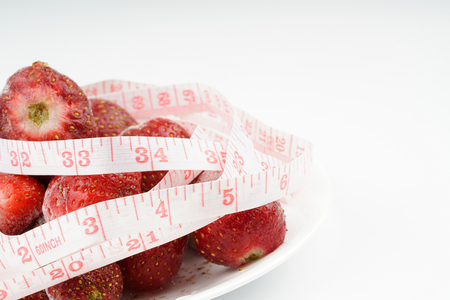 cintas metricas: Frozen strawberries with tape measurement with white background. Diet concept.