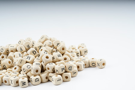 scramble: Wooden letter cube with white background