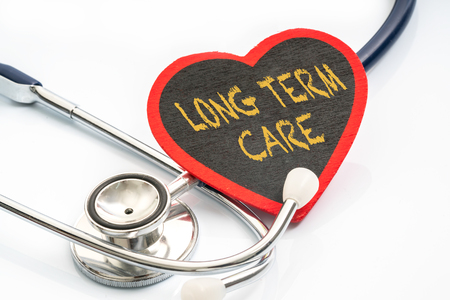 long term care services: Stethoscope and red love with medical conceptual text.