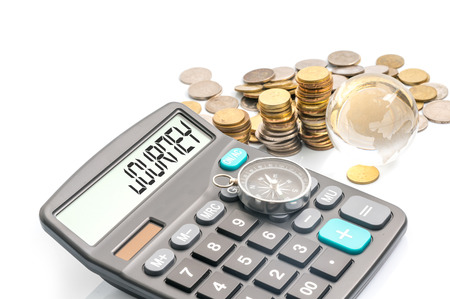 holiday budget: coins, globe, compass and calculator with traveller conceptual text. Stock Photo