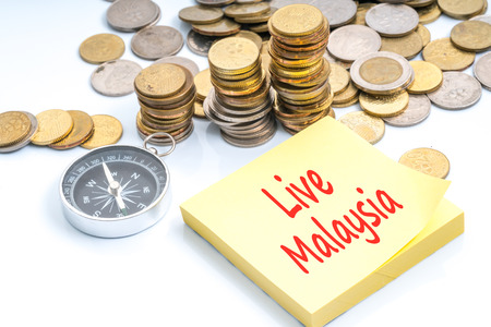 Coins and compass with red text about the best of Malaysia country. Stock Photo