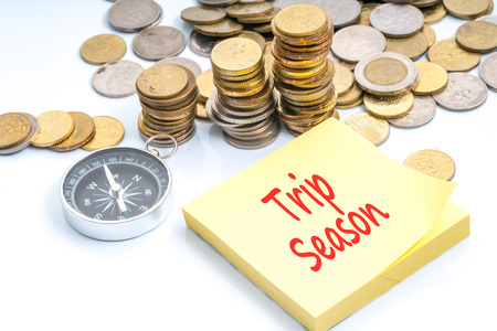 Coins and compass with red text - travel and holiday concept Stock Photo