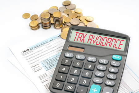 avoidance: Calculator with red text on screen and tax form. Stock Photo