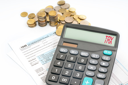 incidence: Calculator with red text on screen and tax form. Stock Photo