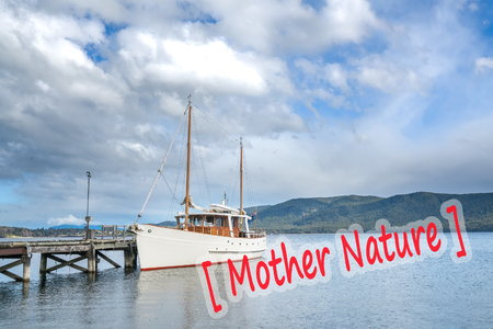 anau: Ship park at wooden jetty with mountain background at Te Anau, New Zealand