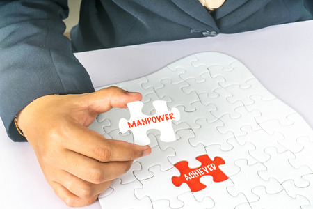 manpower: White jigsaw with text conceptual.