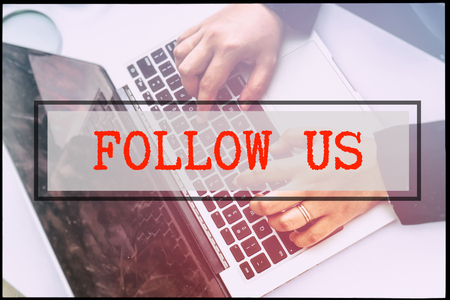 advertise with us: Hand and text FOLLOW US with vintage backgound. Technology concept.