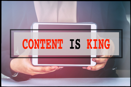 advertise with us: Hand and text CONTENT IS KING with vintage background. Technology concept. Stock Photo