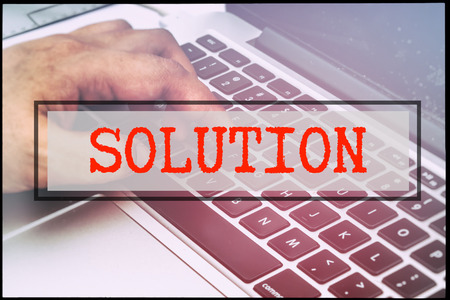 advertise with us: Hand and text SOLUTION with vintage background. Technology concept.