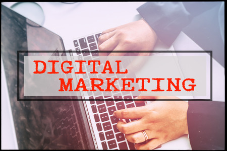 advertise with us: Hand and text DIGITAL MARKETING with vintage background. Technology concept.