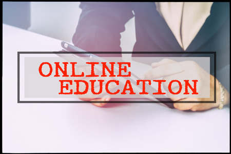 advertise with us: Hand and text ONLINE EDUCATION with vintage background. Technology concept.