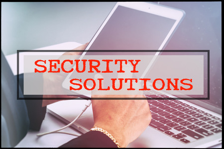 advertise with us: Hand and text SECURITY SOLUTIONS with vintage background. Technology concept.