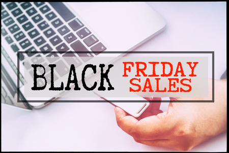 advertise with us: Hand and text BLACK FRIDAY SALES with vintage background. Technology concept. Stock Photo