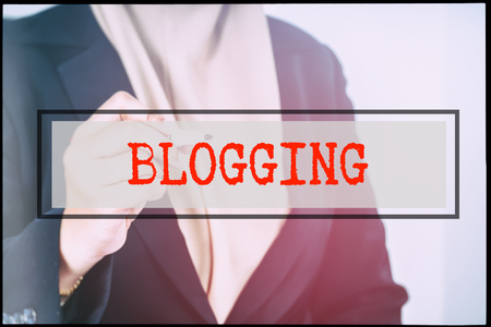advertise with us: Hand and text BLOGGING with vintage background. Technology concept. Stock Photo