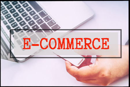 advertise with us: Hand and text E- COMMERCE with vintage backgound. Technology concept.