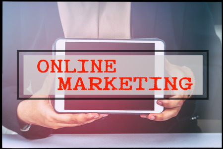 advertise with us: Hand and text ONLINE MARKETING with vintage background. Technology concept.