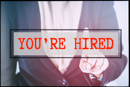 advertise with us: Hand and text YOURE HIRED with vintage backgound. Technology concept.
