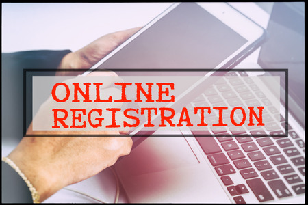 advertise with us: Hand and text ONLINE REGISTRATION with vintage background. Technology concept.