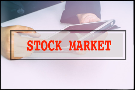 advertise with us: Hand and text STOCK MARKET with vintage background. Technology concept. Stock Photo