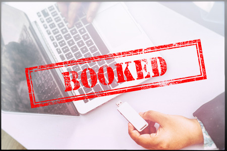 booked: Hand with red grunge stamp with text BOOKED. Technology concept. Stock Photo